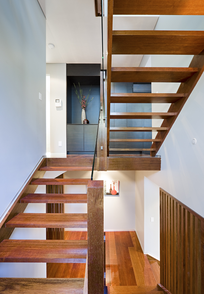 The open design natural wood staircase features glass railings, emphasizing the visual transparency. The upper level features prominent use of dark stained wood cabinetry and wall panels, in contrast with white surroundings.
