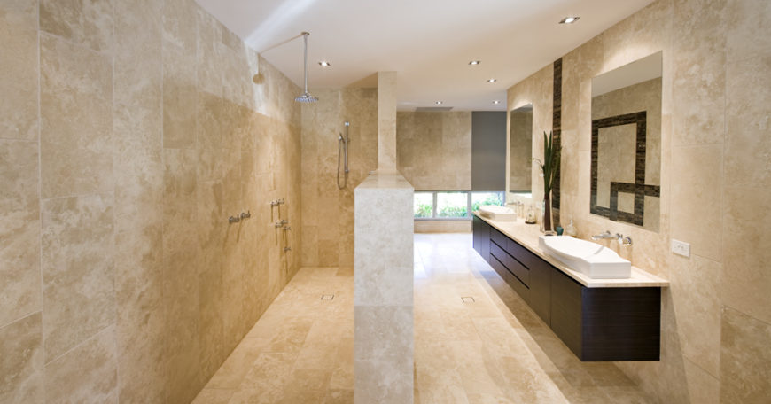 The bathroom is awash in beige marble tiling from the floor on up. A floating dark wood dual vanity with white vessel sinks hangs below a pair of frameless mirrors, while open design shower is seen at left.