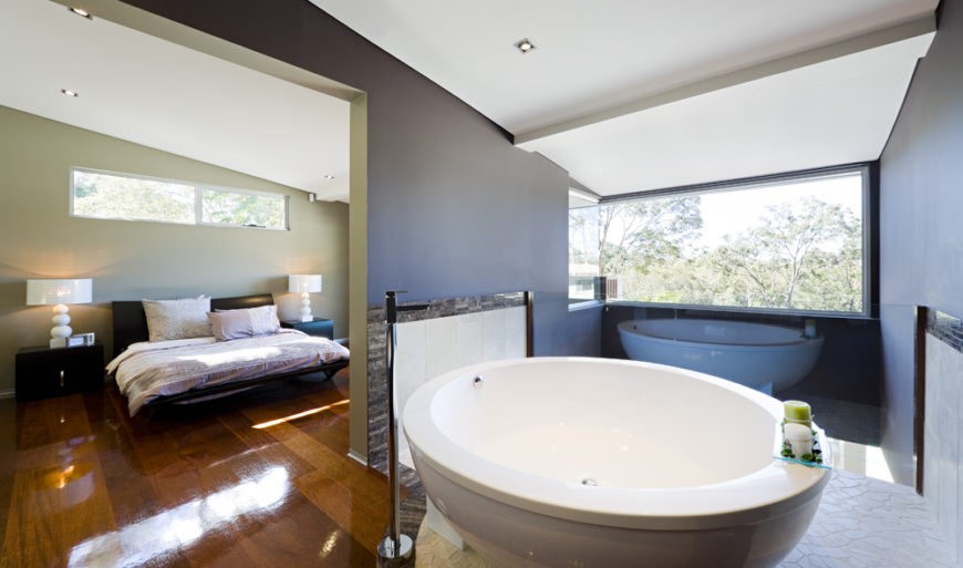 The primary bedroom en suite floats above the open living room, with only a glass panel separating the space. A large circular pedestal tub stands at center, surrounded by organic textured white tile.