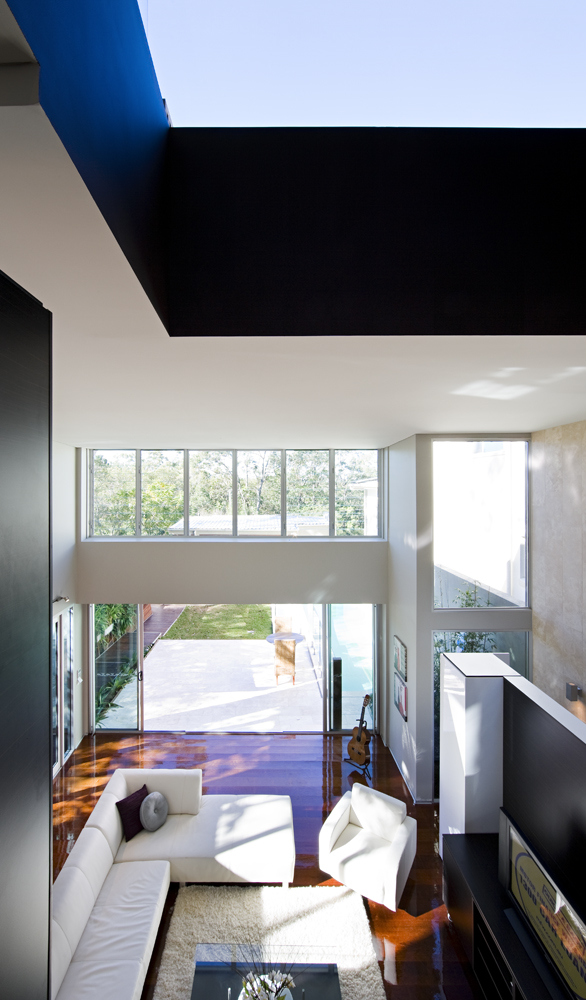 Looking down toward the living room rom above, we can see the high contrast between stark white furniture and sleek hardwood flooring. The lengthy backyard is seen through wide open door panels and full height windows.