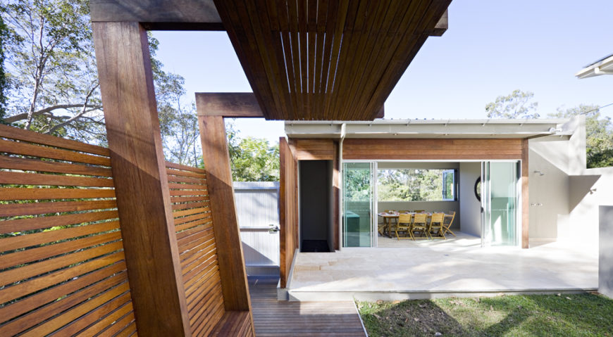 Returning to the back yard, we see the well appointed pool house, reflecting the home design with retractible glass panel doors of its own. A large patio wraps around, with storage set off to the side of the structure.