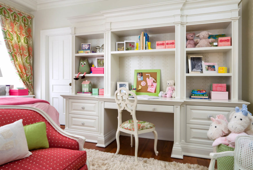 A close-up of the large desk with glass pulls and lots of shelving. The main workspace is large enough to accommodate a computer at a later date, and the height is enough to grow in. The back of the desk is wallpapered in a pretty cream stylized floral pattern.