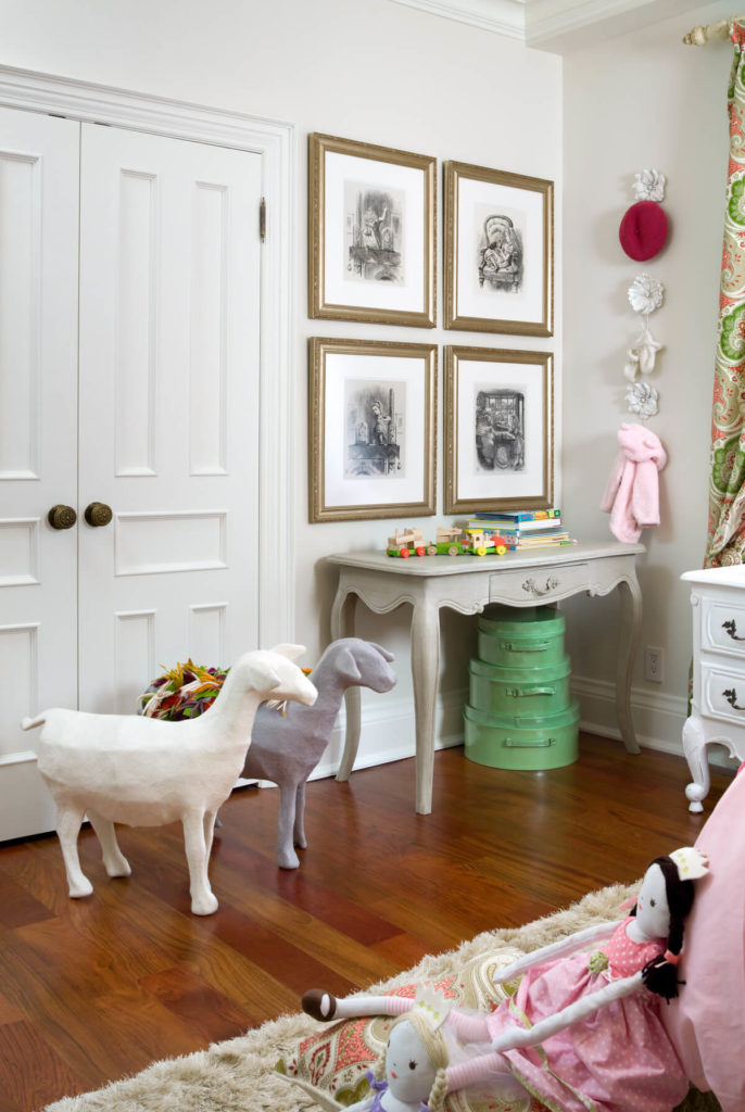 The rich hardwood flooring is covered by a soft, faux fur rug in taupe. Adorable felted goats are positioned in front of the sizable closet, next to a side table topped by vintage prints in gilded frames.