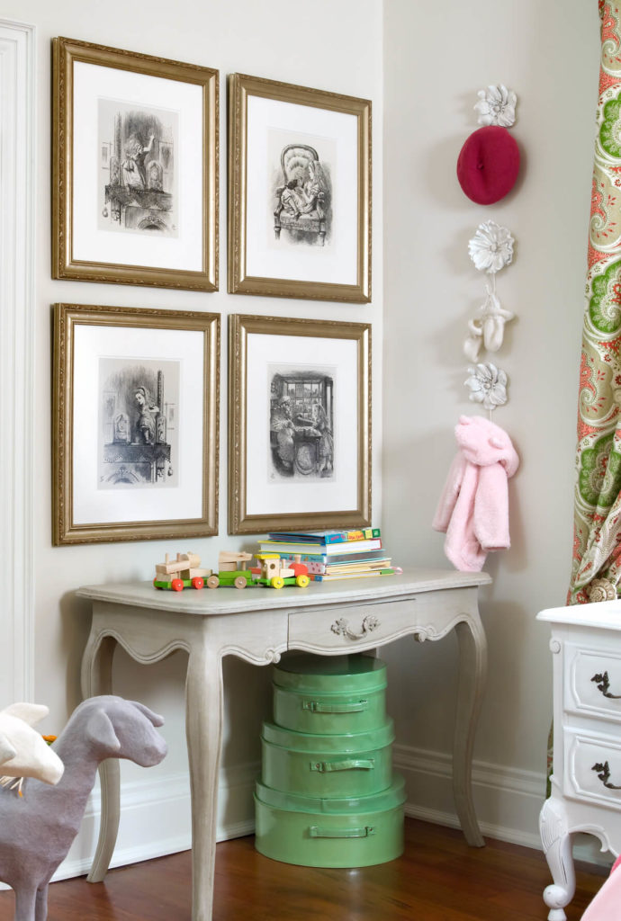A close-up of the side table in taupe, with vintage luggage stacked beneath it as decoration. Alice In Wonderland prints hang above the table, and next to it is a series of floral hangers.