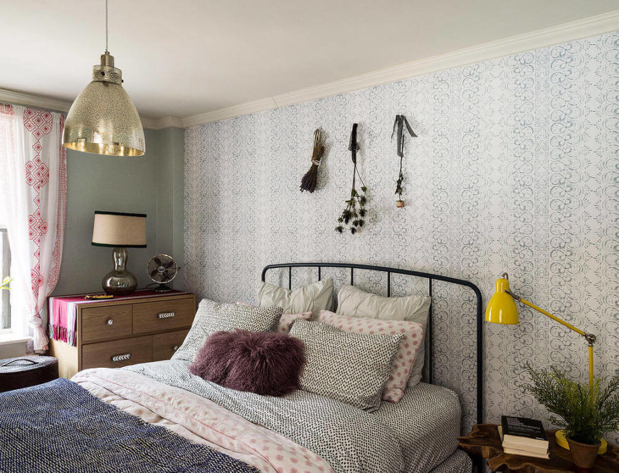 """The bedroom was designed as a cool oasis, with soft tones and a light, airy feel. """"Racy Lacy"""" removable wallpaper floats above the textural bed, while the gold pendant light highlights the center of the room."""
