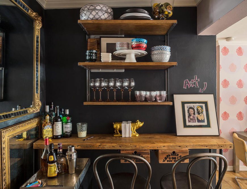 The small kitchen is enlivened with both industrial and vintage touches, with a personalized chalkboard wall floating above. Rustic wood countertop here serves as dining space for two.