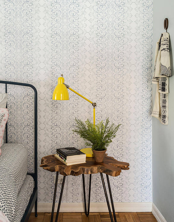 Bedside table is a cross section tree slice over thin metal legs. Color pops in this space, courtesy of a bright yellow arched lamp.