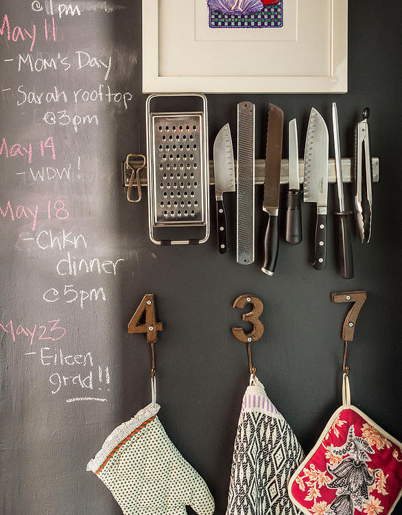 """Magnetic knife rack and """"number"""" hangers cling to the chalkboard wall, here adorned with calendar notes."""