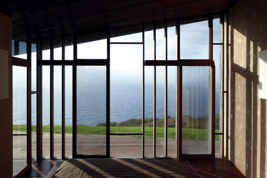 Here we have a view of the ocean from one of the bedrooms. Thin wood beams minimally obscure the expansive vista.