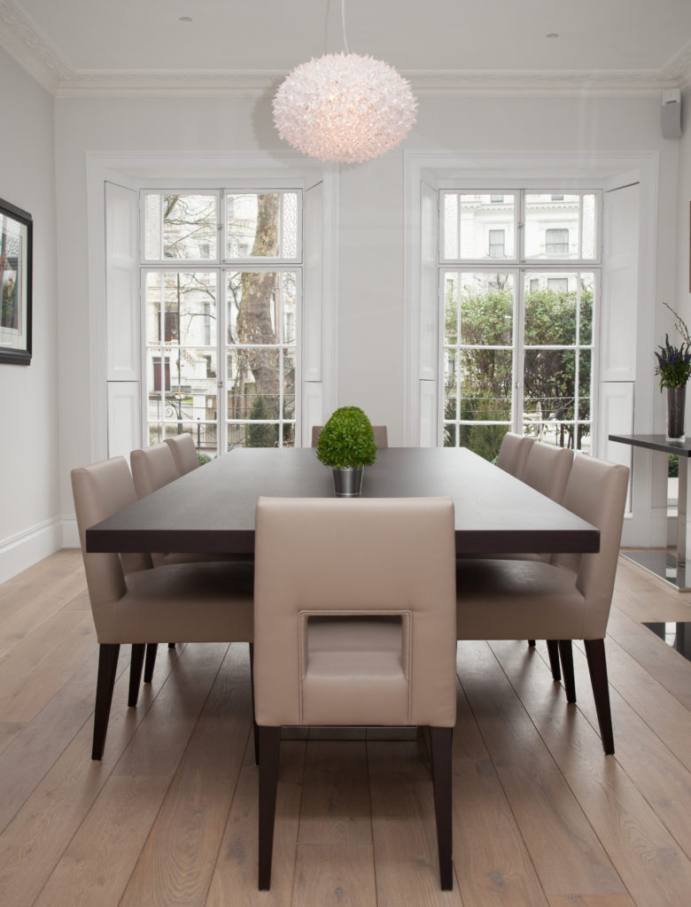 A classic dining room highlighted by a charming crystal chandelier along with light hardwood flooring. It is framed with light gray walls and white glass windows.