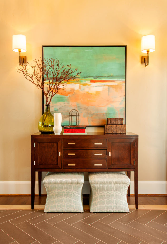 A close-up of the sideboard, with two little upholstered stools tucked neatly beneath. The artwork behind it on the warm beige walls adds a splash of contemporary color.