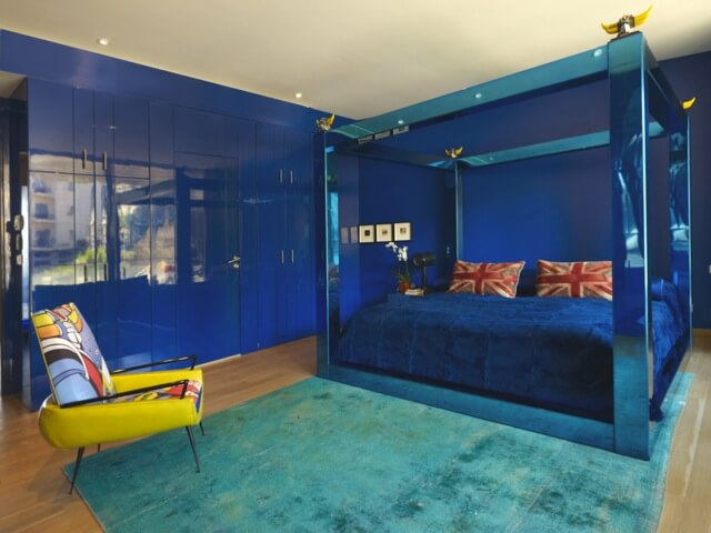 The primary bedroom is boldly colored in blue. The walls are a glossy, deep blue with storage all along the left wall. The four-post bed is in metallic blue, with velvet bedding and two Union-Jack pillows. An aqua rug and a brightly colored chair add a bit of color variety.