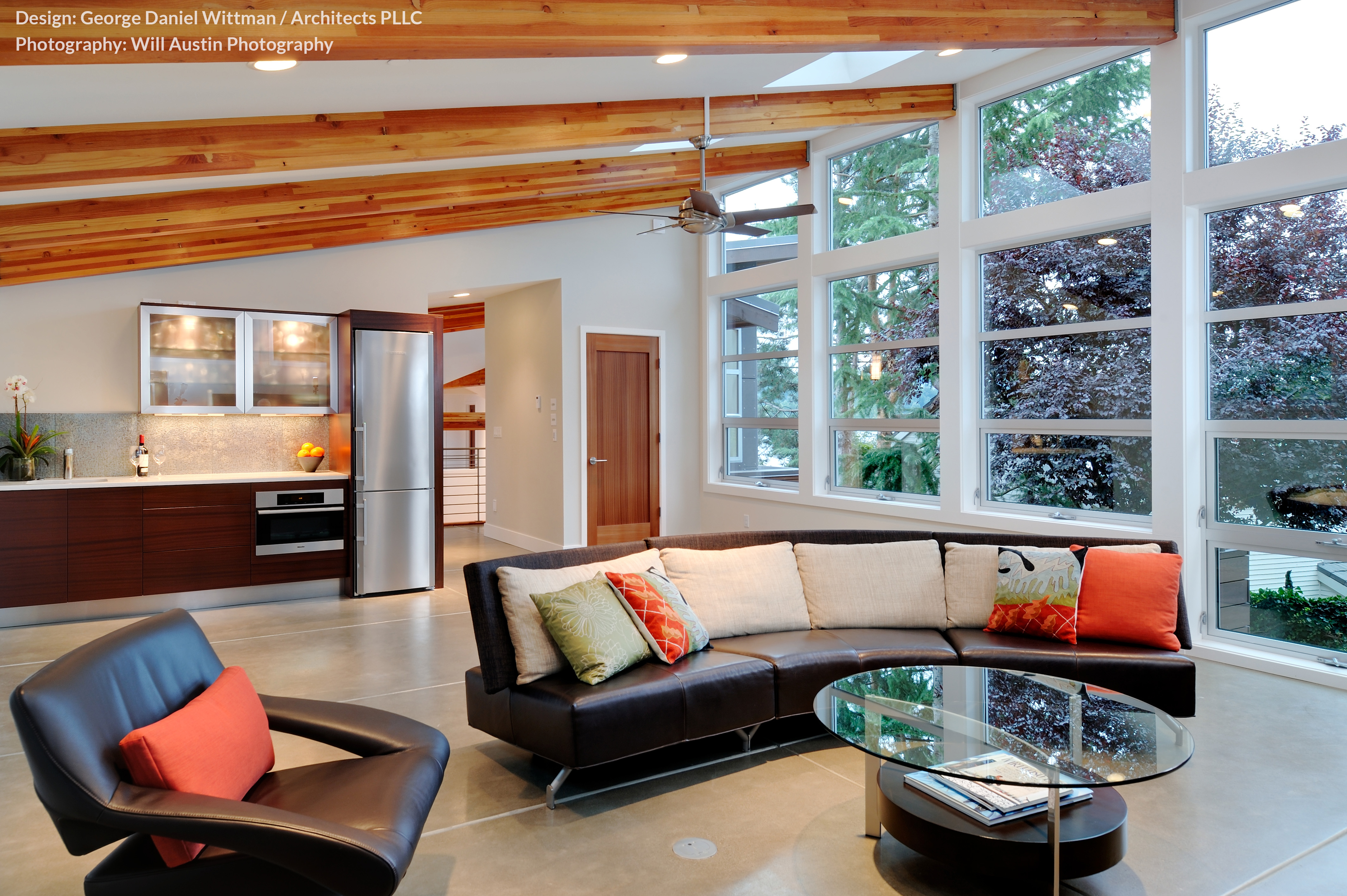 This larger living room space stands under an expansive sloped ceiling, where exposed beams meet the floor to ceiling array of windows at right. Curved dark leather sectional and modern accent chair pair with a multi-tiered wood, metal, and glass coffee table.