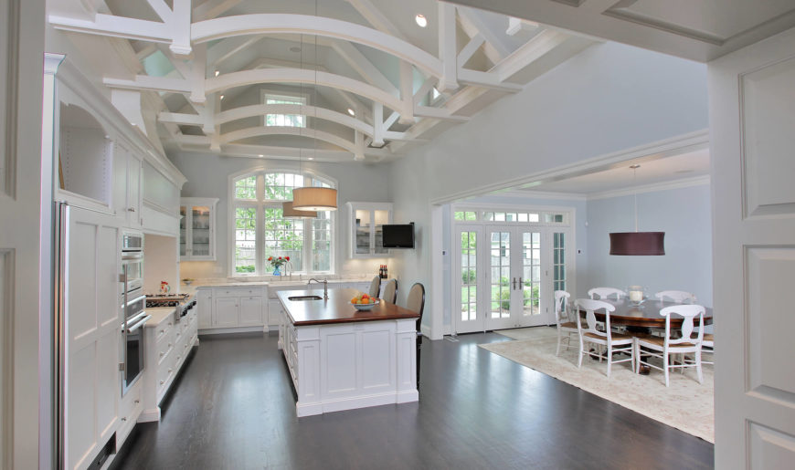 Huge white kitchen with dark wood floors and open white beamed ceiling by GTM Architects