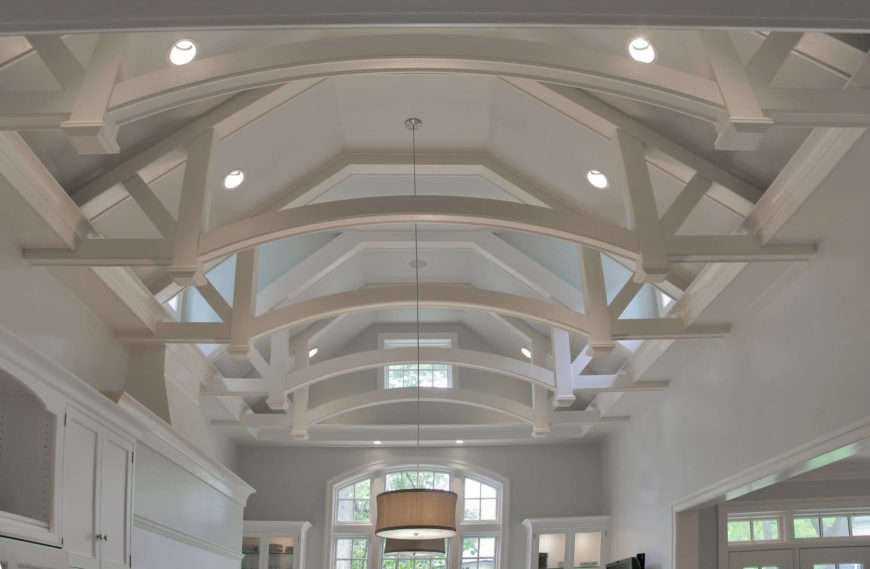 Detailed look at the ceiling reveals intricate, transitional style beam work, with curved arches bridging the center, inspired by an old church photograph. Dormer windows are barely visible flanking the room.