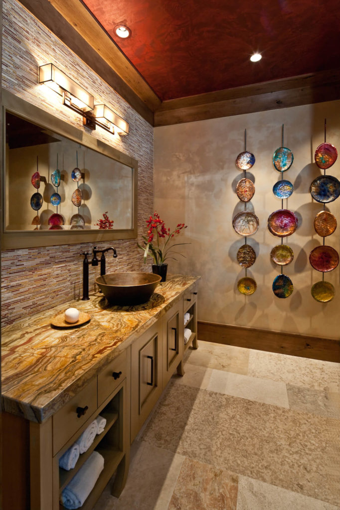 This bathroom, in contrast, features rich earth tones, with natural wood vanity cupboards and copper vessel sink over the marble countertop. Micro-tile backsplash and brightly colored wall plates add playful detail.