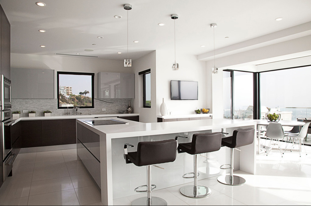 The kitchen is defined by this L-shaped island, featuring cooktop space and room to spare for dining. Sleek white countertops mirror the large format tile flooring.