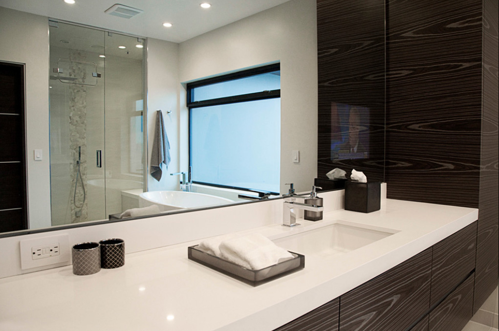 This bathroom continues the high contrast look of the kitchen, with dark wood cabinetry below a thick slab white countertop vanity. In the mirror we see a white pedestal tub beneath a large window, with glass enclosure shower in background.