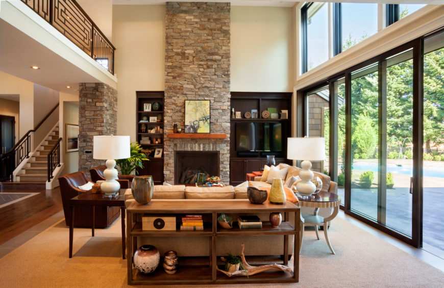 A straight on view of the living room shows every little accent and detail that creates a home that feels lived-in and has personality. Built-in bookcases on either side of the fireplace.