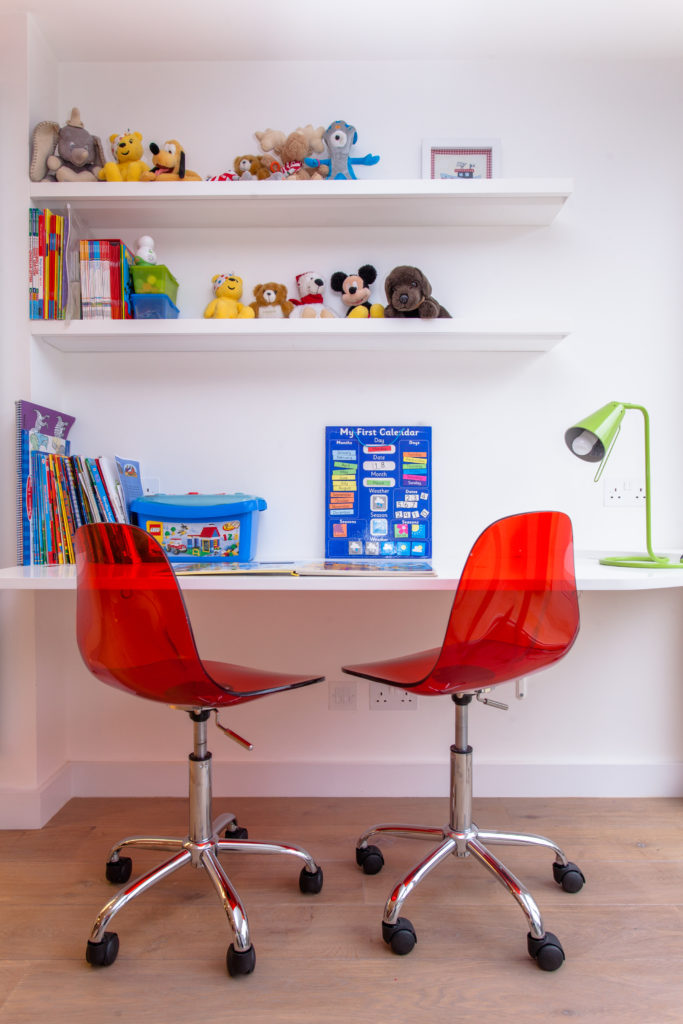 The playroom is where a wild array of color sprouts within this home. Here, a pair of red acrylic seat chairs stand below a built-in desk and book shelving in white.