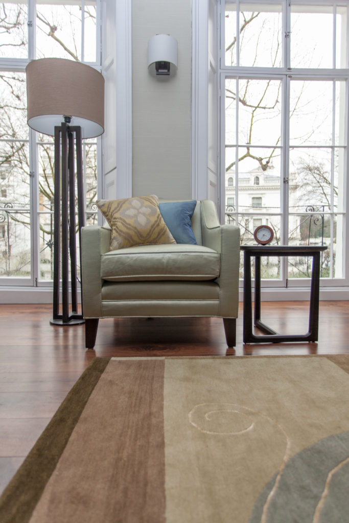 The living room holds earth toned seating and area rug over rich hardwood flooring. This club chair is flanked by an angular side table and floor lamp, with large, full height windows in background.