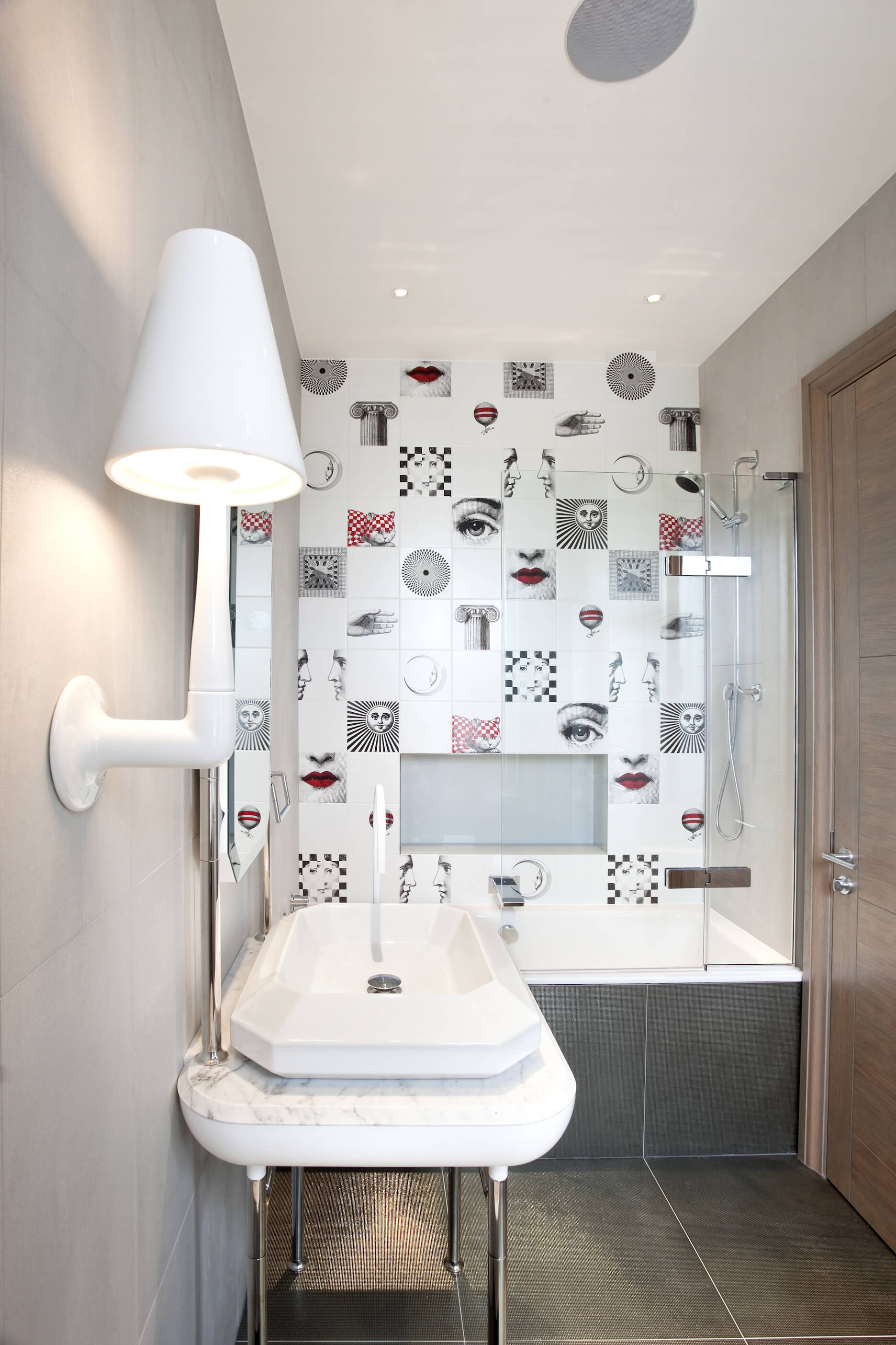 In another bathroom, we see a free standing marble topped vanity with extra wide vessel sink over grey large format tile floor. Glass enclosure shower sports unique art piece tiles for a playful look.