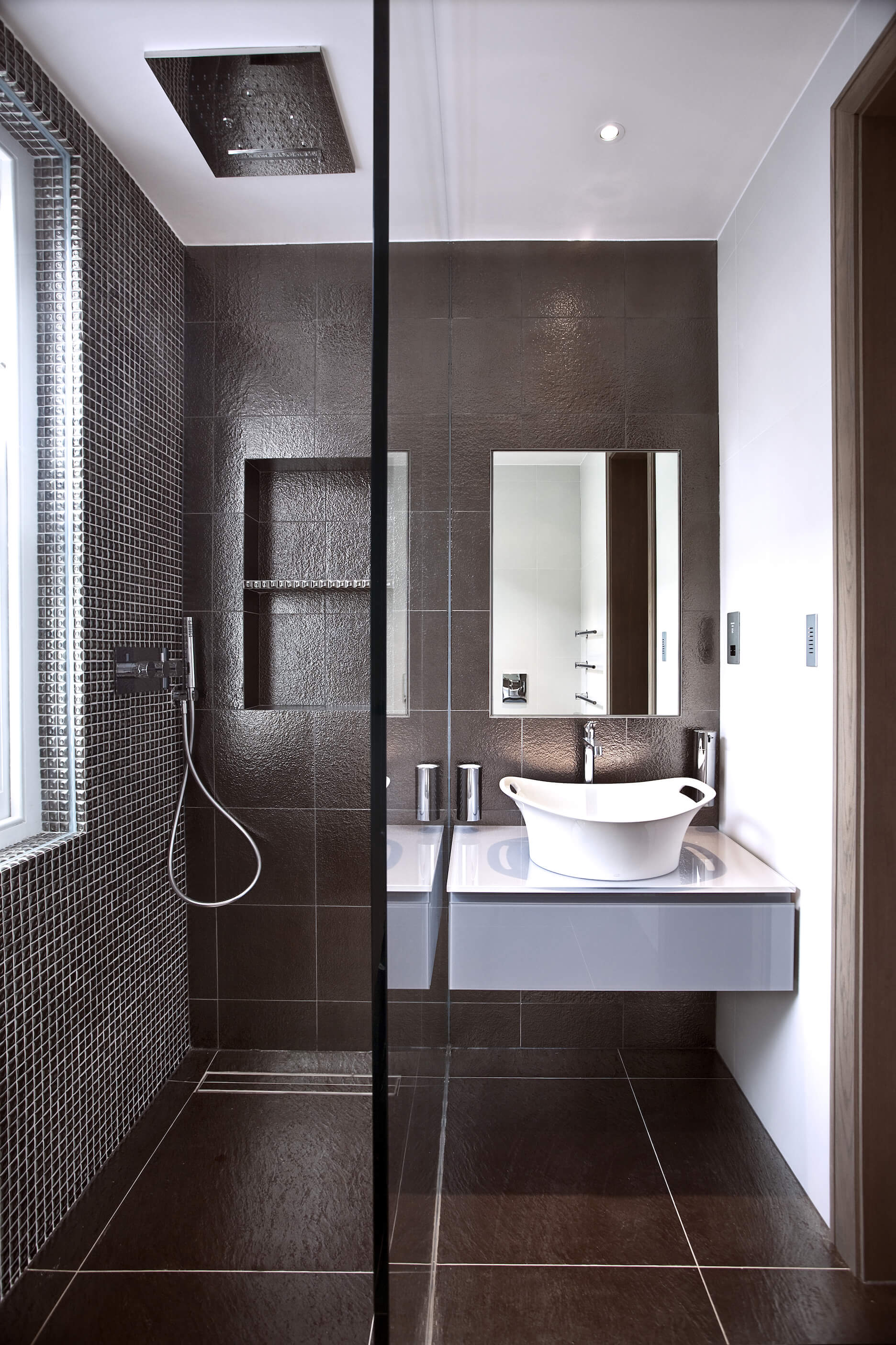 Another bathroom with dark tile flooring holds this compact space, pairing a white floating vanity with handle-rimmed vessel sink next to a glass enclosure shower with rainfall head.