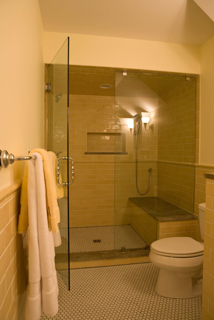 The large walk-in shower is fully glass-enclosed, with soft beige tiling throughout over white micro-tile flooring.