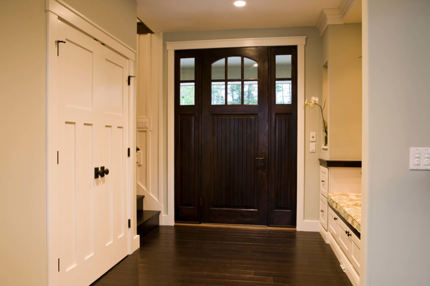 The main entryway features extensive espresso-stained bamboo flooring, matching the tone of the hardwood front door. Storage options abound here.
