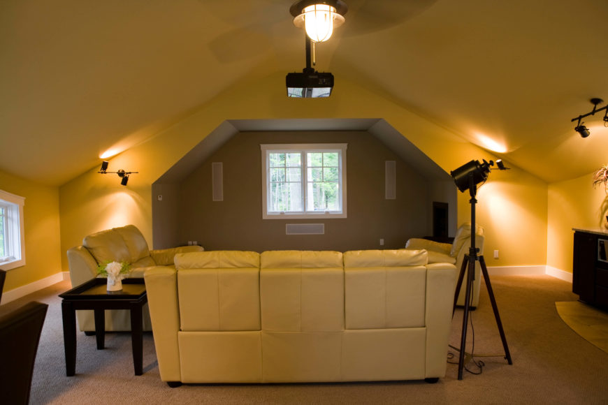With a low vaulted ceiling and arched entertainment space, this room is perfect for family movie night. The soft hued walls and light beige carpet contrast with black tables and cabinetry.