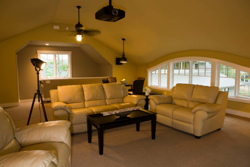 Upper level family room is a perfect space for entertaining and watching movies, with a projector hanging over a trio of plush leather seating options and jet black coffee table. A wide span of windows allows for natural light, while film-set-style floor lamp helps set the mood.