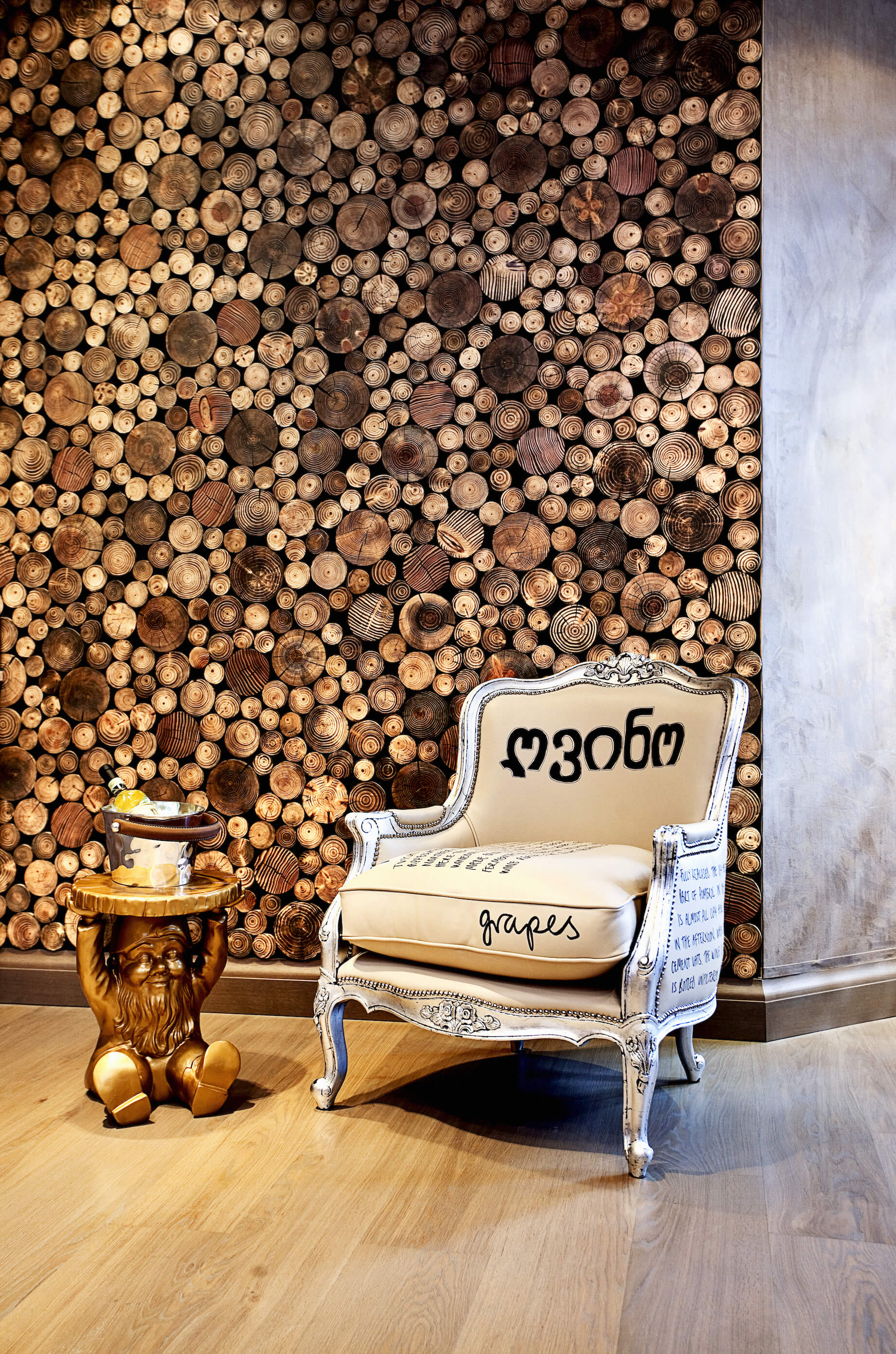 This transitional room contains a unique wood cross-section wall, standing in contrast with an ornate camel back chair painted with silver and text. A small kitschy gnome table coated in gold stands beside.