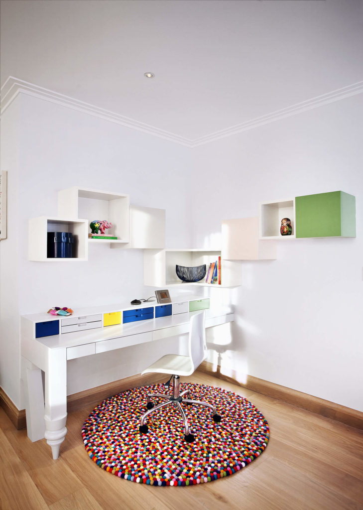 The home office space stands a minimalist wall-mounted white desk and cubic shelving with bursts of color over hardwood flooring. Bright, multicolored gum ball rug holds the sleek contemporary office chair.