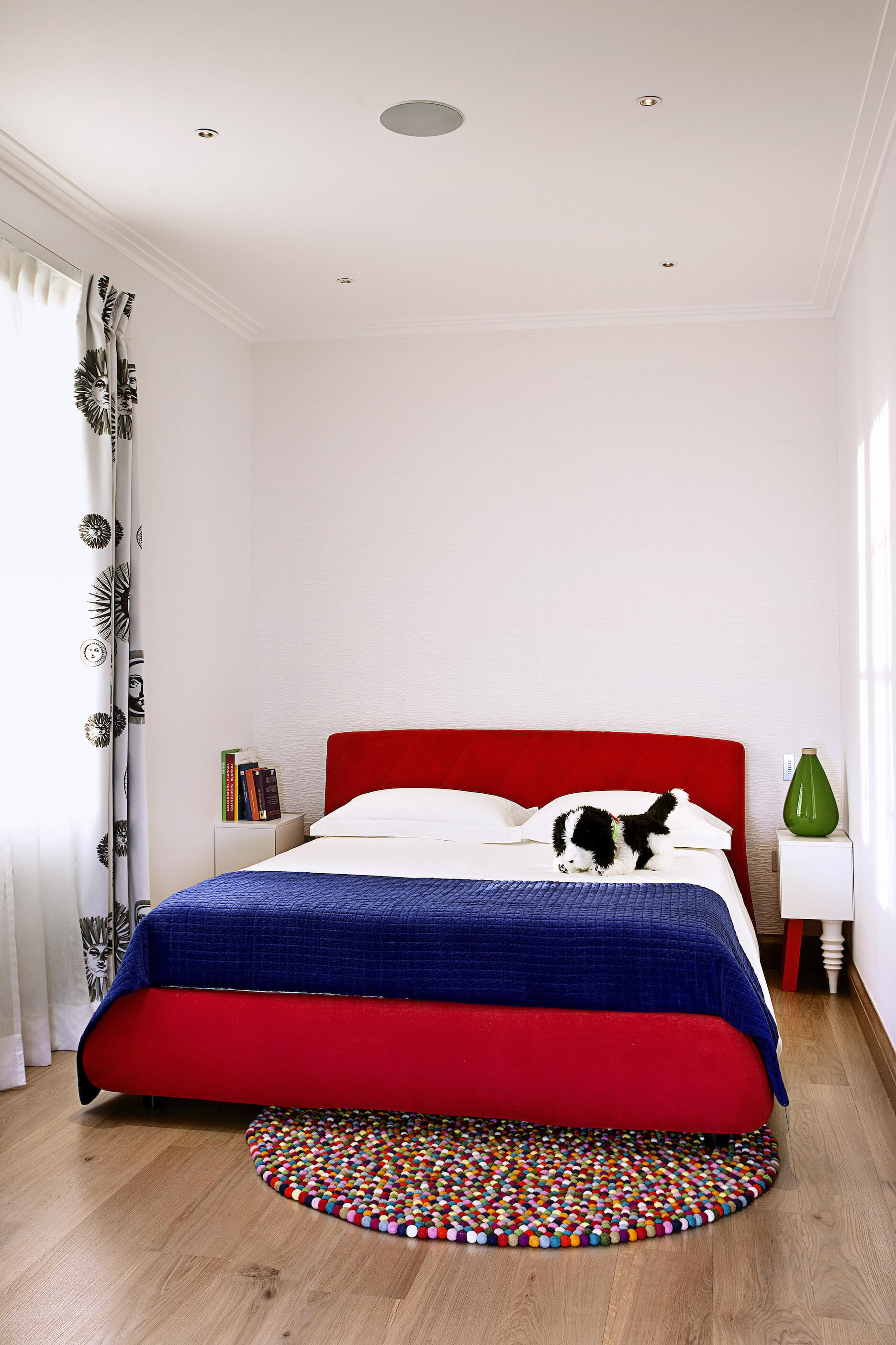 In this bedroom, we see another rainbow hued gum ball rug beneath a large red framed bed with blue and white sheets. The bed is flanked by a pair of white tables with mismatched legs.