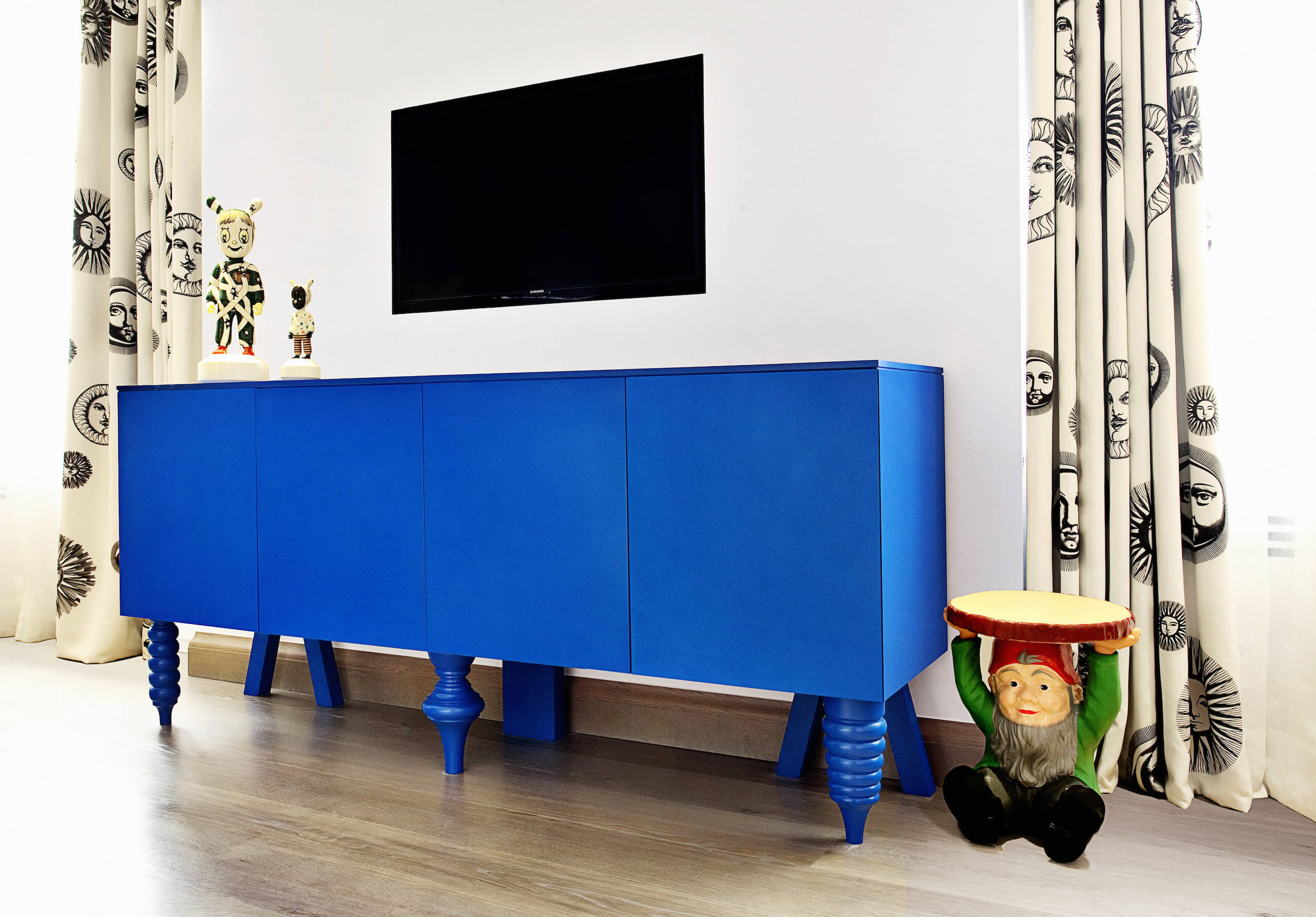 The bedroom holds another bold piece of furniture; this bright blue cabinetry standing between sun-patterned drapes, with a mismatched leg set. Wall mounted television hangs above the space, sporting another gnome table and pair of small statues.