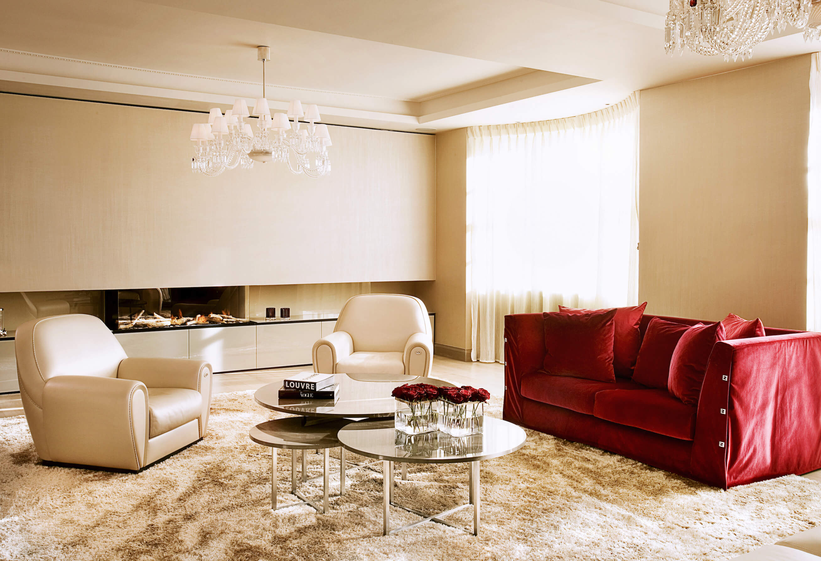 Richly designed gold-hue living room with red sofa by Roselind Wilson Design