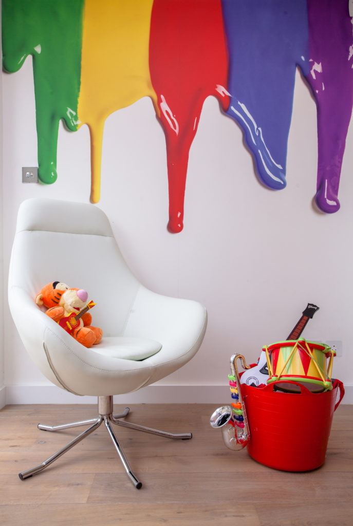 In more striking use of wall decals, this area of the room holds a large format rainbow paint-spilling image above a white leather reading chair and toy bucket.