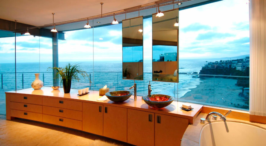 The primary bathroom hangs a pair of vanity mirrors in front of the expansive exterior glass, over a natural wood countertop. Large soaking tub at right enjoys the ocean views or can be made private via full height curtains.