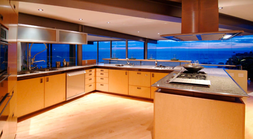 The open kitchen stands at the center of the home, overlooking an array of rooms below the large windows. Countertops float above the wood cabinetry, with subtly recessed lighting above.