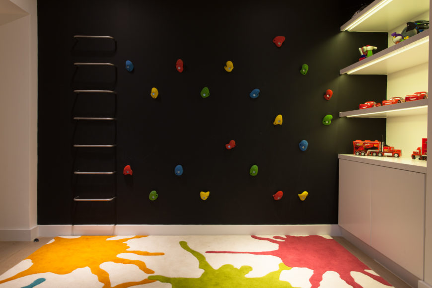 The far end of the kids' space features a black climbing wall next to elegant, inner-lit shelving for the toy collection. Splatter paint rug unifies the look.