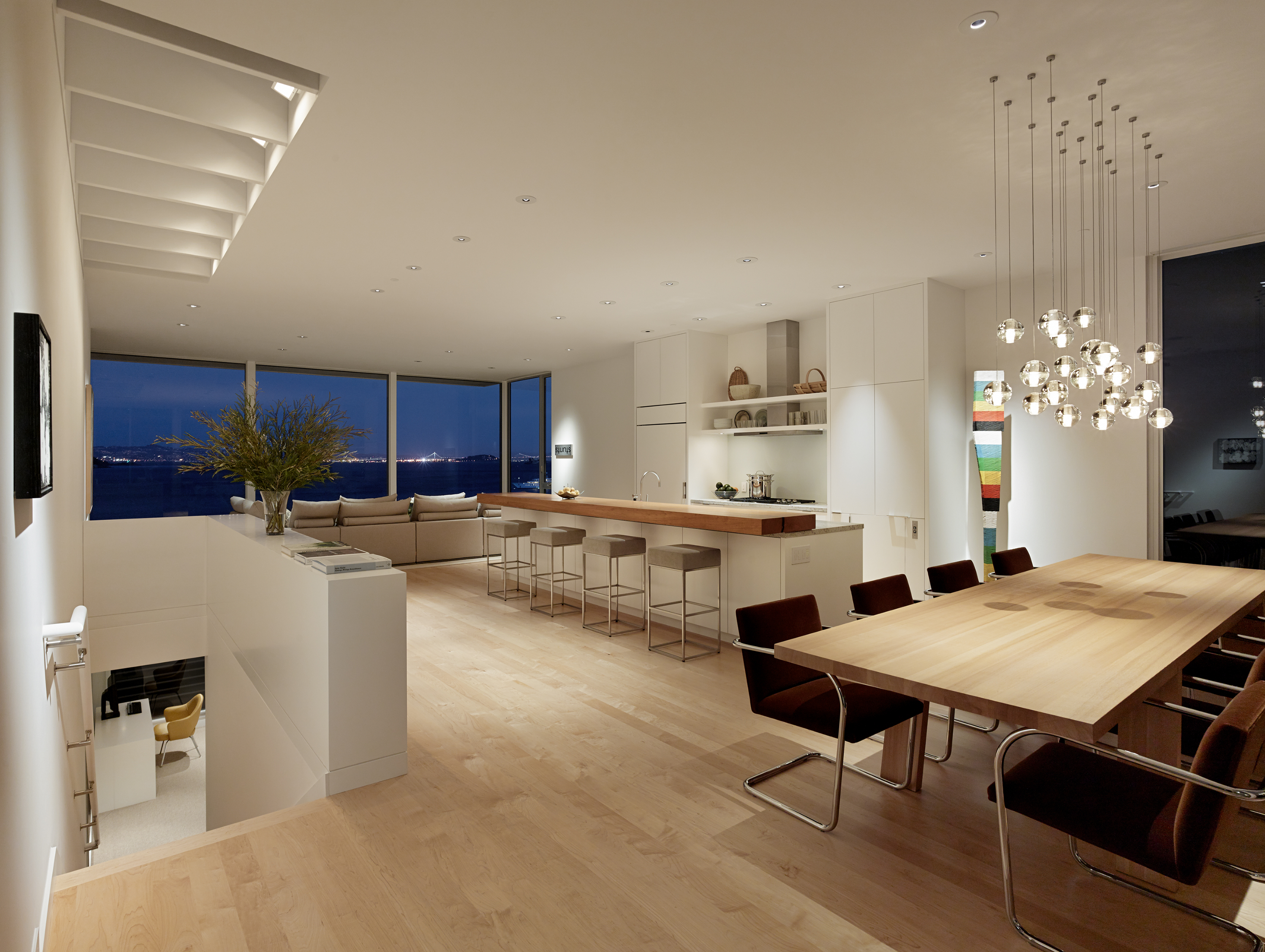 The view at night from the same spot highlights the city lights across the bay. The light fixture sparkles beautifully above the table, and recessed lighting keeps the rest of the space well-lit. The minimalist design allows the views to take full effect.