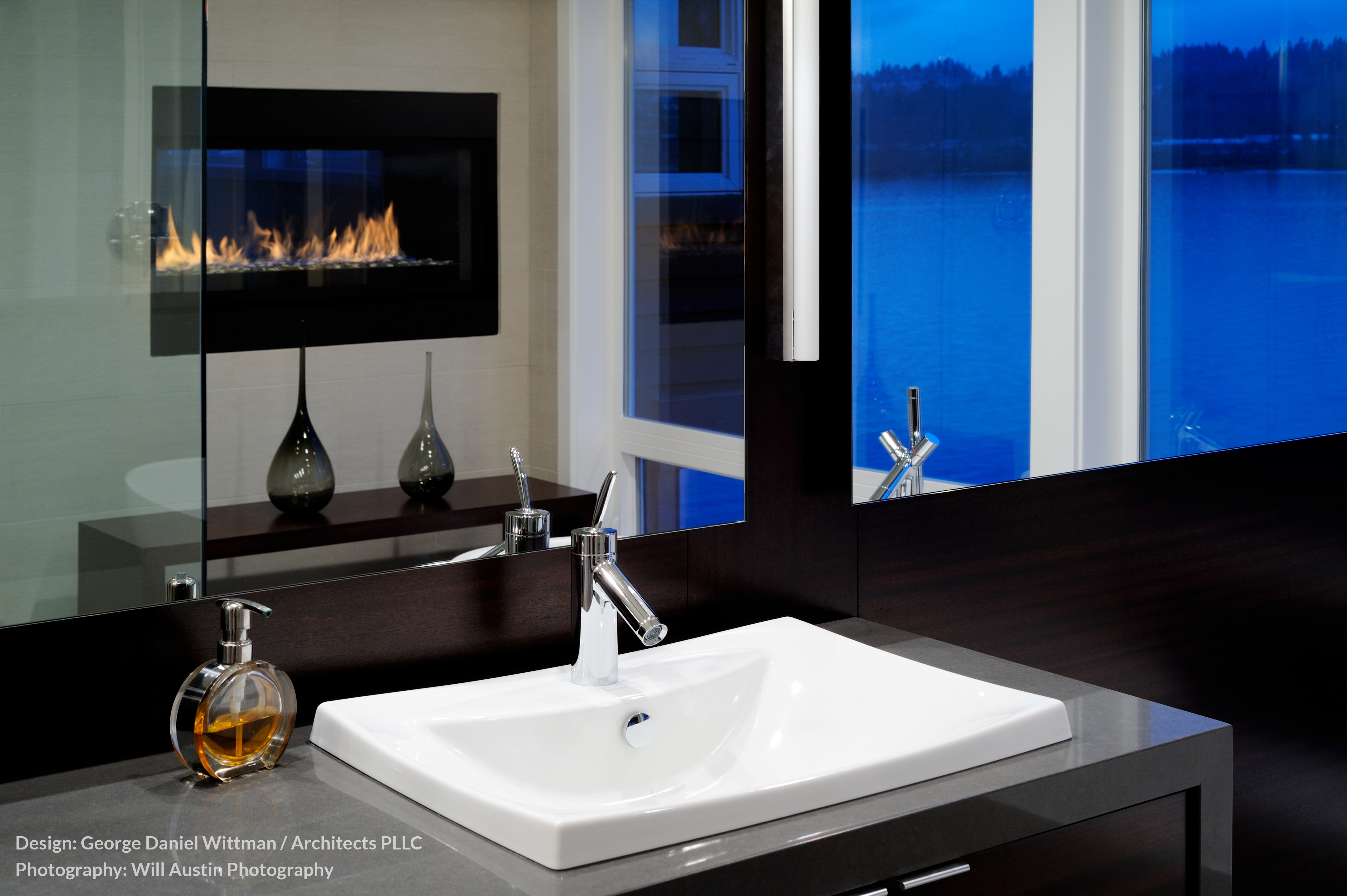 The primary bath, in contrast with the rest of the home, is awash in dark tones. The dual vanity stands below a dark wood wall framing a trio of large mirrors, reflecting the gas fireplace.