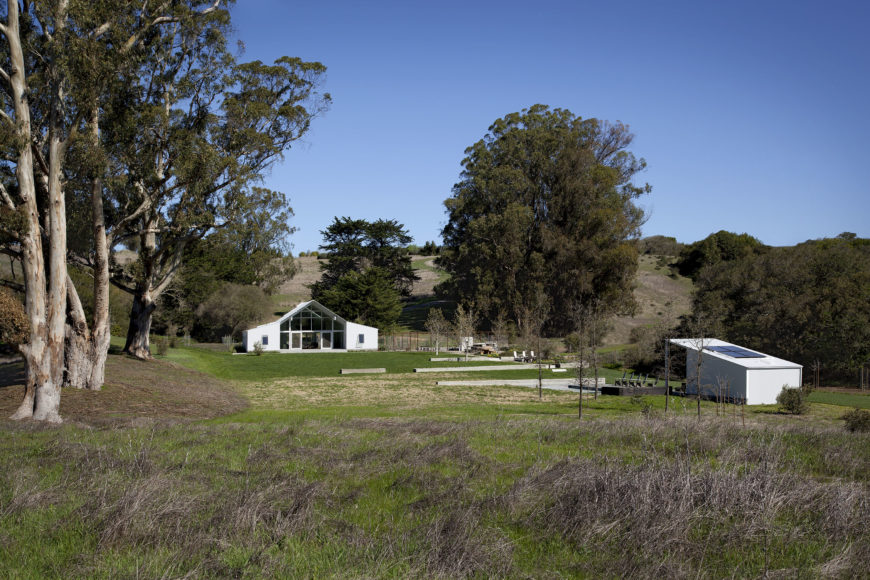 This wide view of the ranch puts the barn house and accompanying pool house into context, revealing the gently hilly landscape within which it fits. The angular white structure's facade is dominated by glass panels for a transparent look.