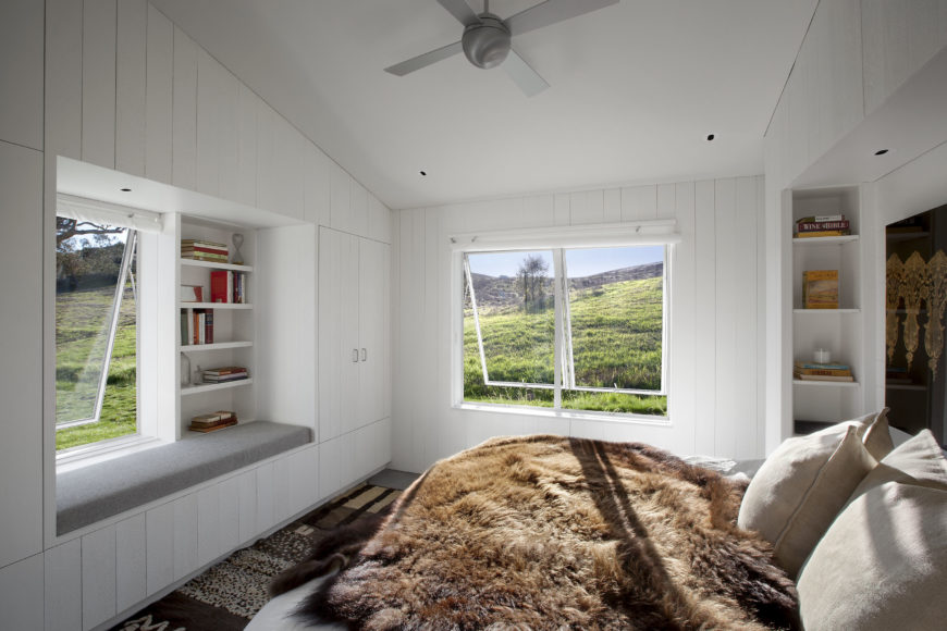 Airy primary bedroom features white shiplap walls and vaulted ceiling. The bed is covered with a brown fur blanket that complements the brown rug.