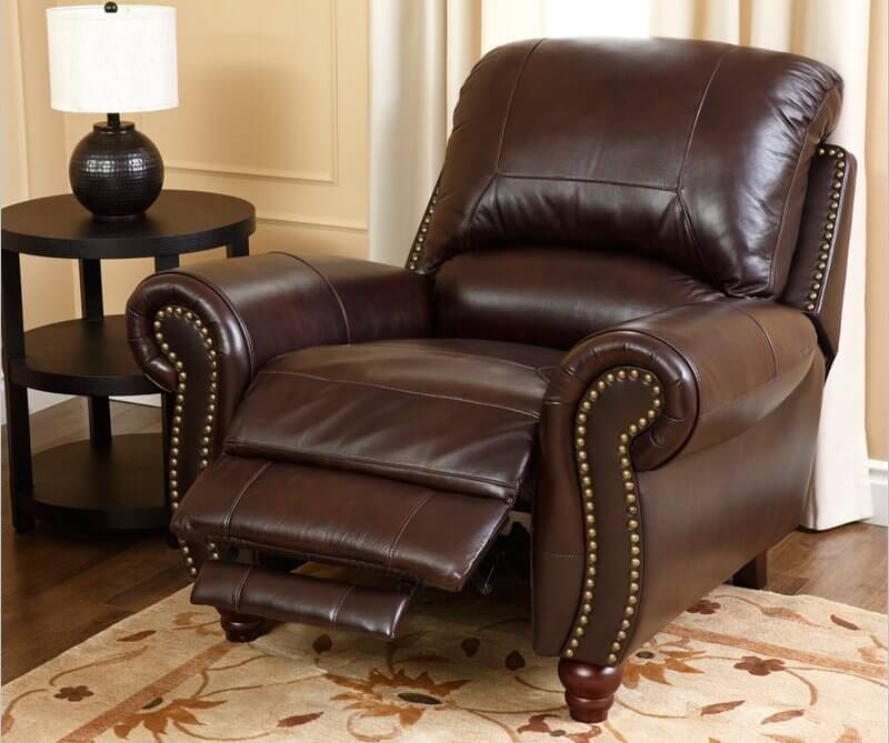 This luxurious leather recliner features nail head trim, thick cushioning on the seat and back, and a wide footprint flanked by roll arms.