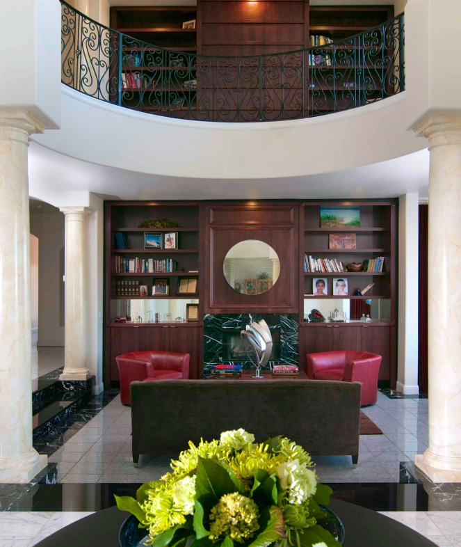 From the bottom of the foyer, the lower half of the library is open on three sides, differentiated from the rest of the room by the marbleized gold columns. Through the iron railing of the balcony we can see the rich wood of the extended library.