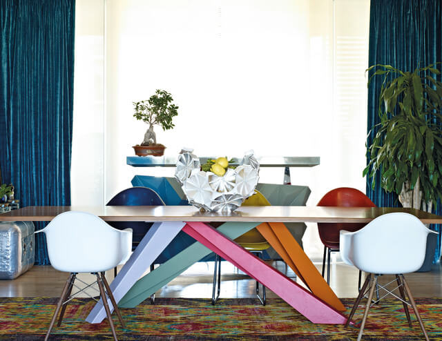 The long dining table is topped with natural light wood, but the legs of the table are pink, orange, teal, and periwinkle, arranged in a criss-crossing style. Multi-colored bucket seats serve as dining chairs, and a geometric, asymmetrical fruit bowl acts as a centerpiece. Metallic blue curtains hang on either side of the large window. A table sits in front of the window, with a bonsai tree.