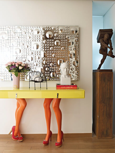 The hallway has a side table with glossy orange mannequin legs in heels serving for table legs. The yellow table is topped by a geometric mirrored artwork. To the right is a classical style sculpture.