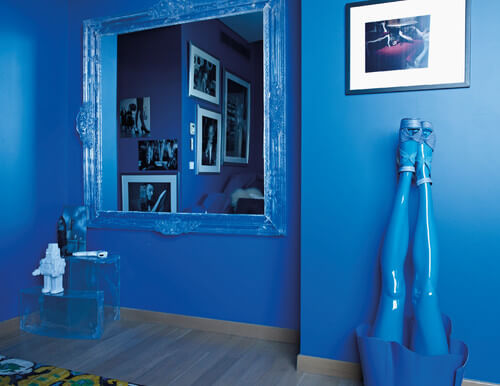 The bedroom has further unique blue accents, including a pair of upside-down blue mannequin legs in heels, and a mirror in a painted ornate frame. Clear stacking boxes act as shelving in the corner.