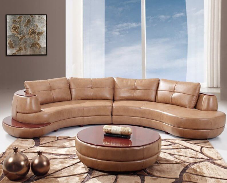 This two-piece curved leather sectional features a rounded edge shape with rich wood plating on the top and small side platform. Matching ottoman coffee table at center features the same wood tabletop.
